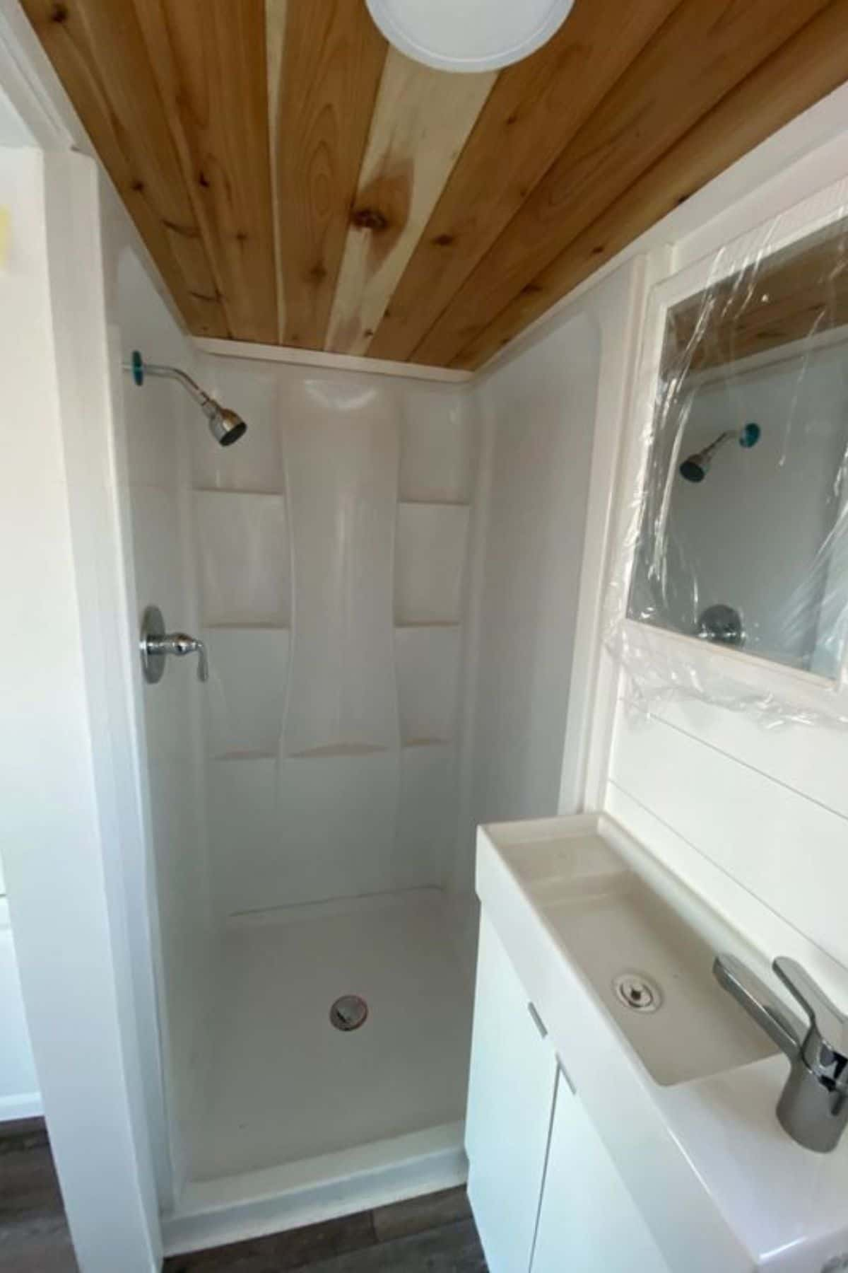 white shower with built in shelves next to petite white sink