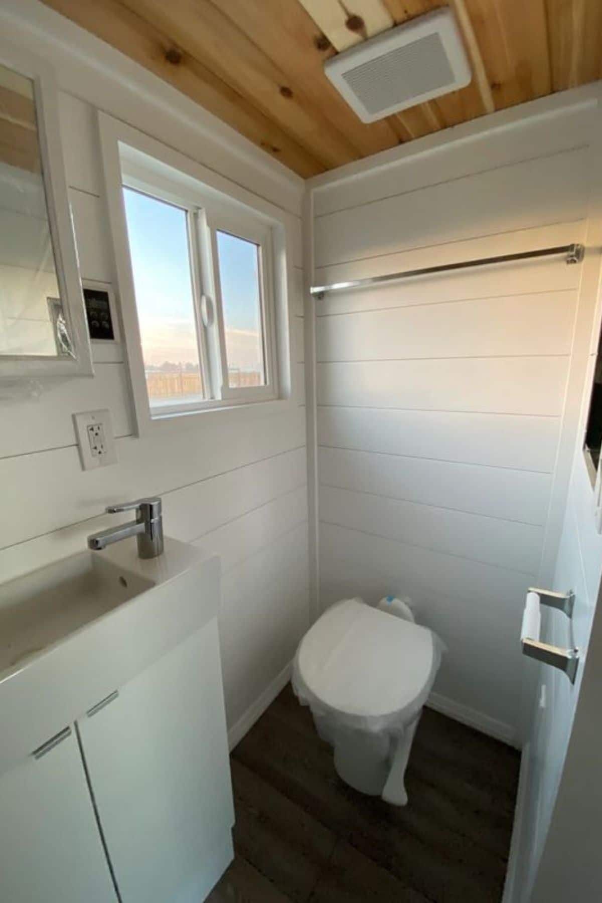 compost toilet against white wall beneath towel rack