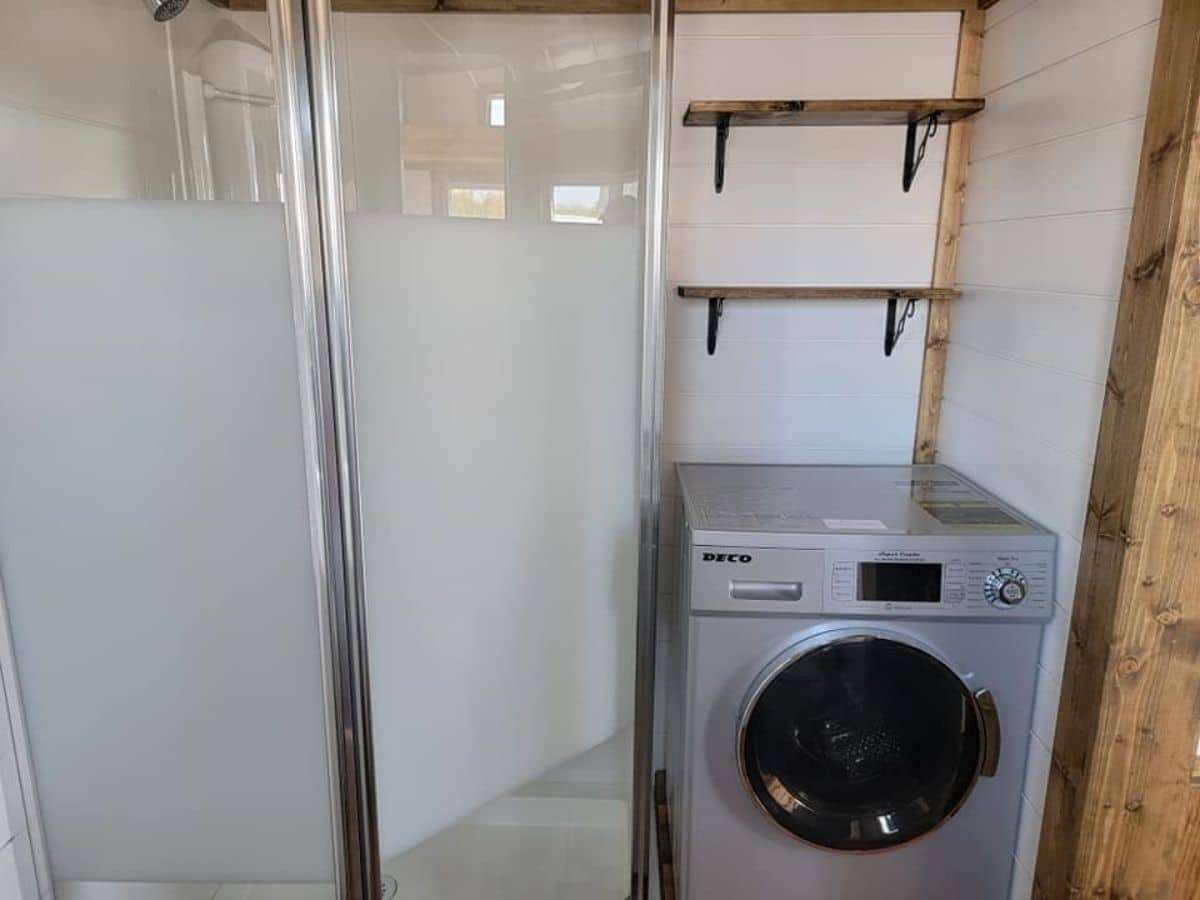 combination washer and dryer beneath shelves by shower stall