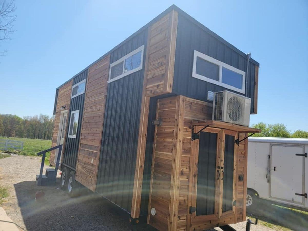 back of wood tiny home with black siding trim