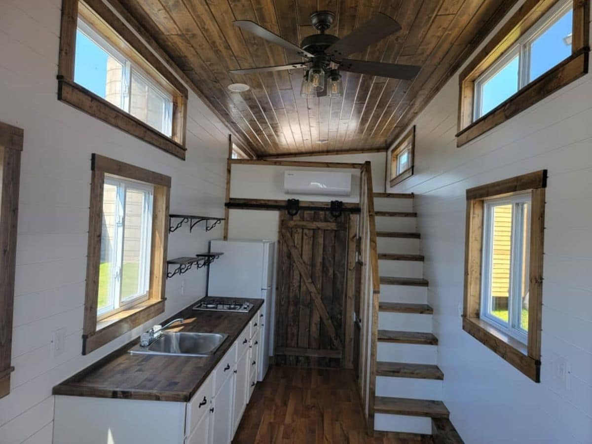 kitchen counter on left with stairs on right in tiny home