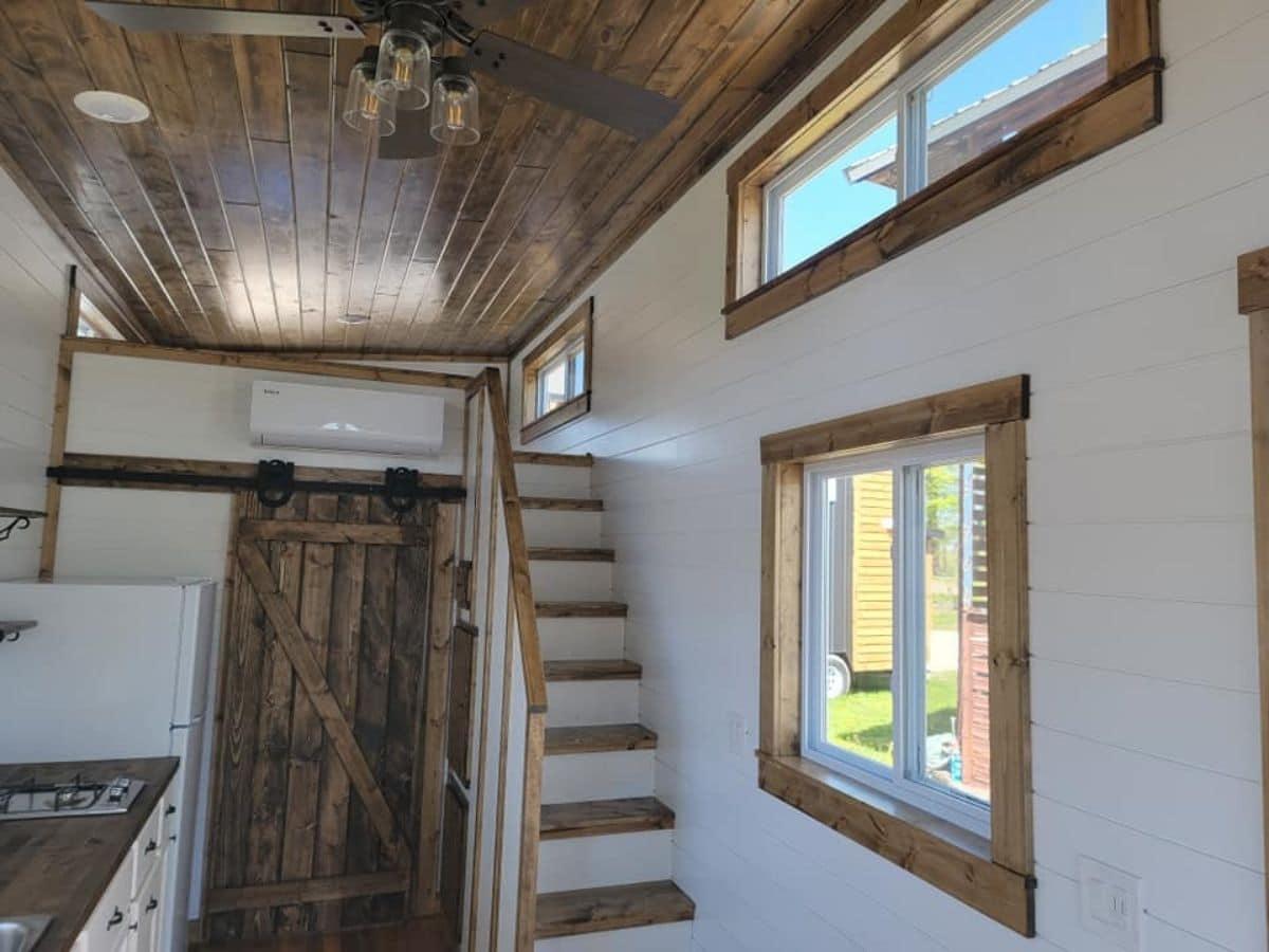 wood stairs leading to loft by barn door bathroom door
