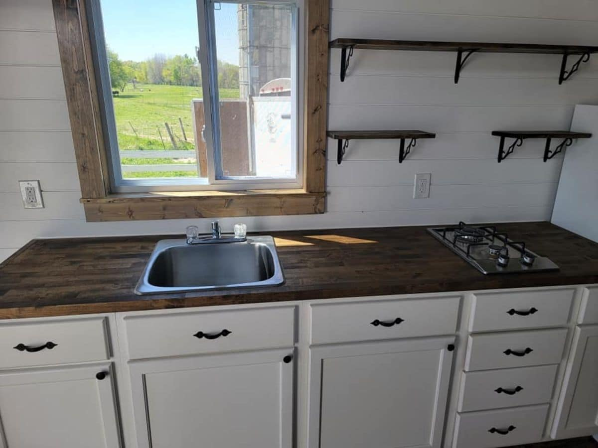 stainless steel sink in wood countertop above white cabinets