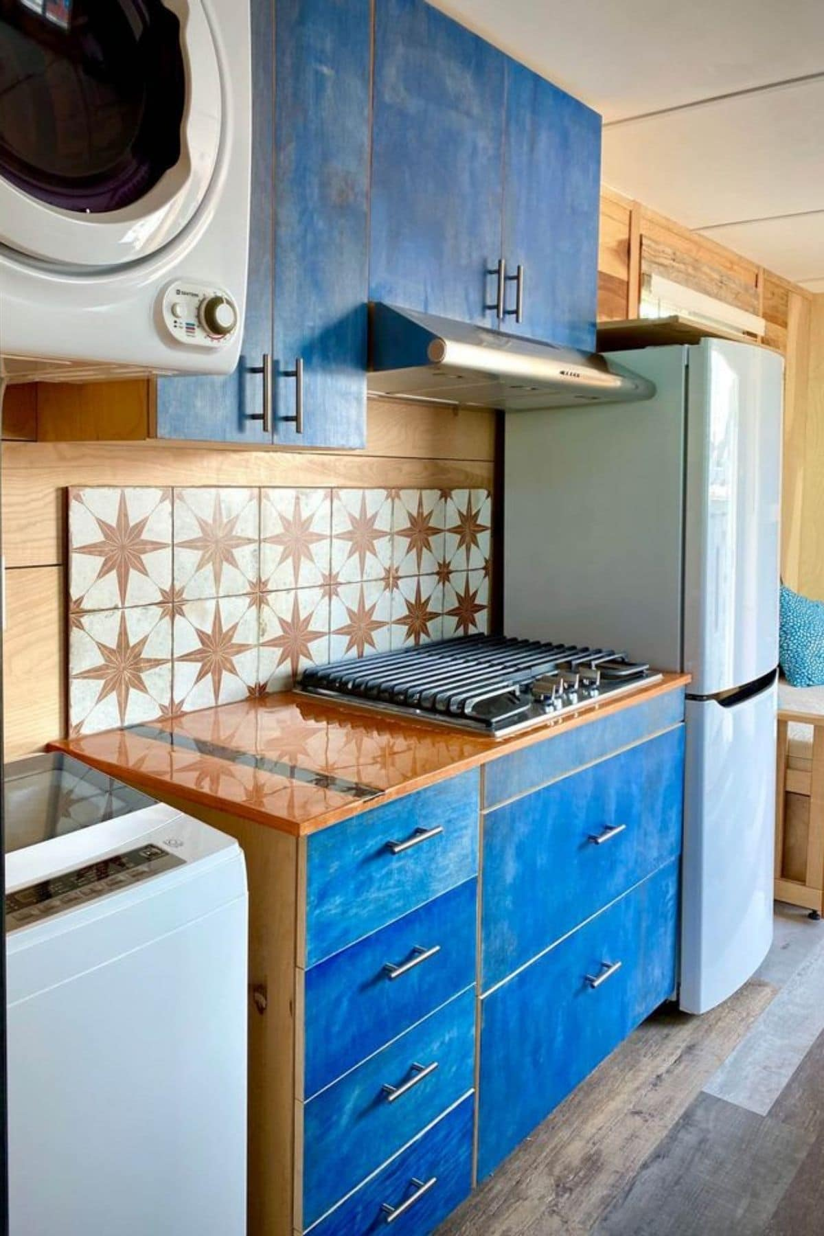 kitchen with orange and whtie tile backsplash and blue cabinets