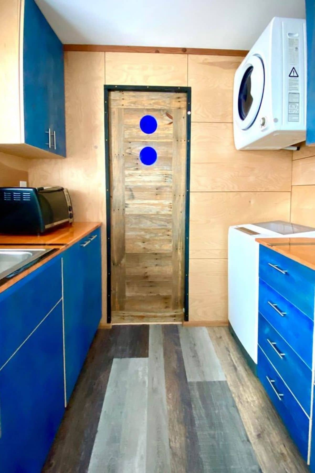 wood door with blue accents at end of kitchen