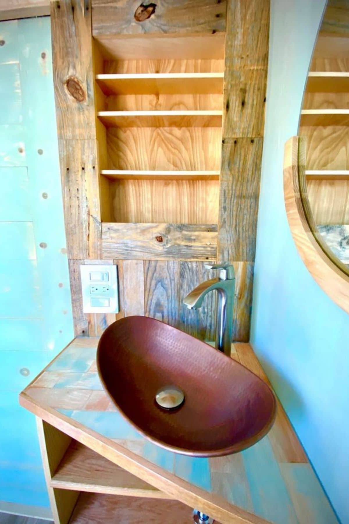 brass sink on reclaimed wood counter with teal walls