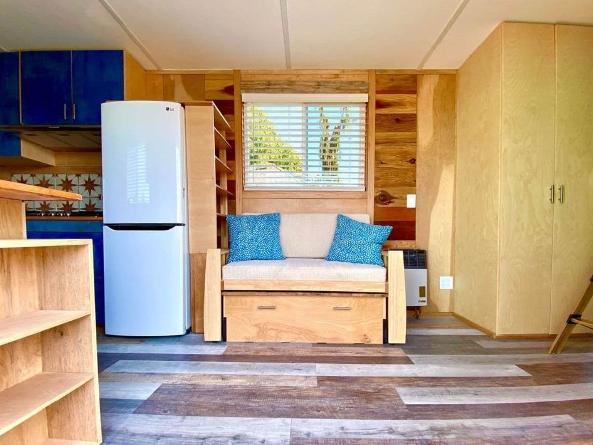 Wooden bench next to white refrigerator with blue pillows