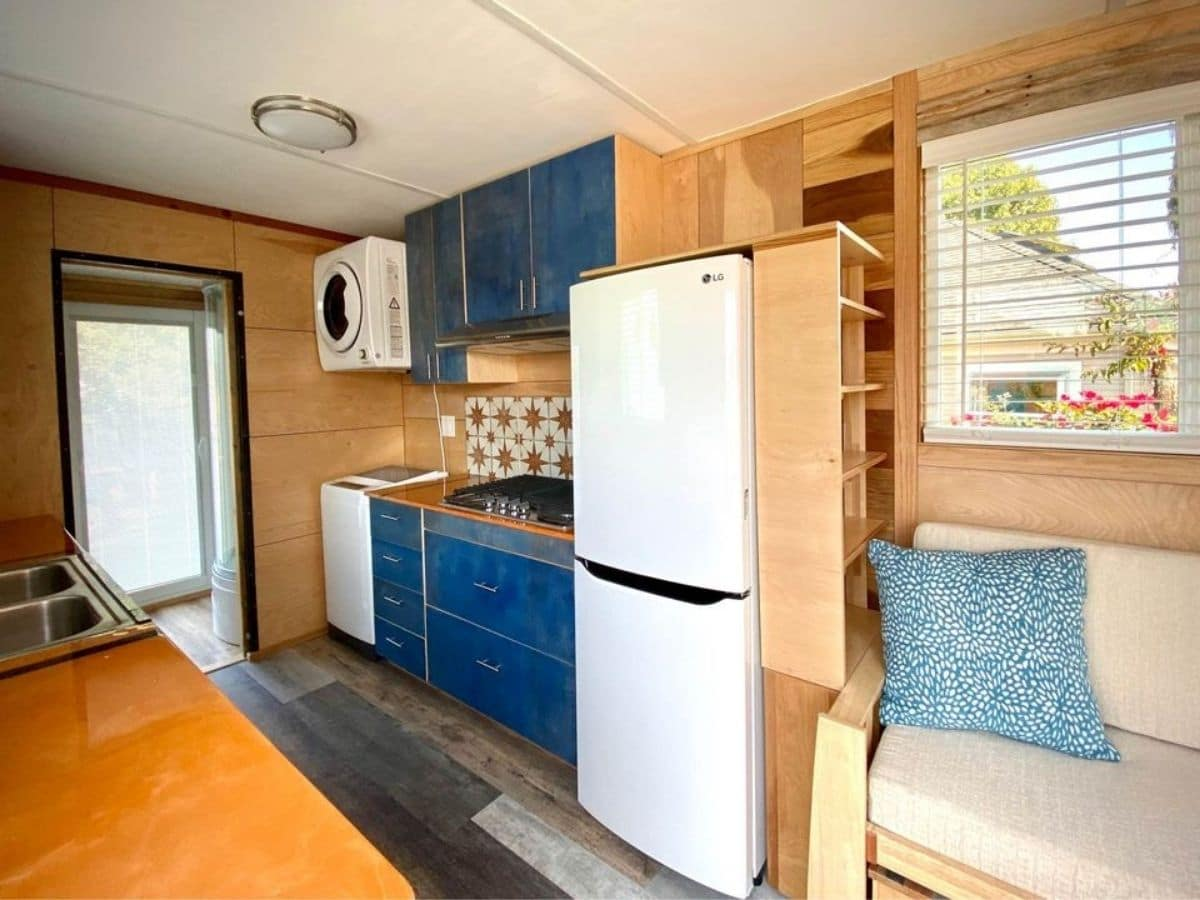 kitchen on side wall with blue cabinets white refrigerator and stacking washer and dryer