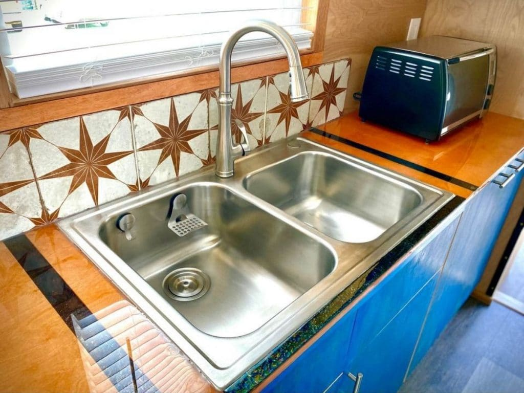 double stainless steel sink in counter against orange and white star tile backsplash