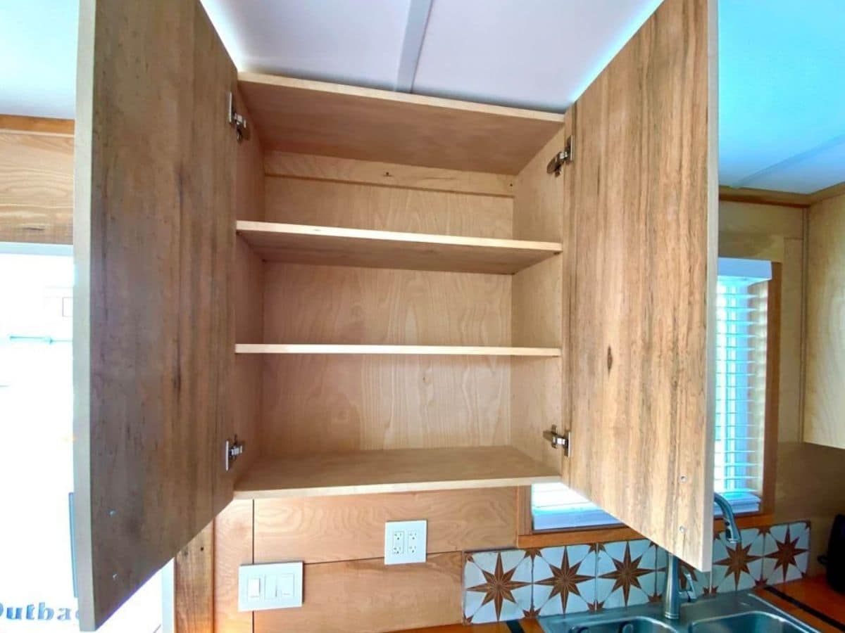 open wood cabinet above counter in kitchen