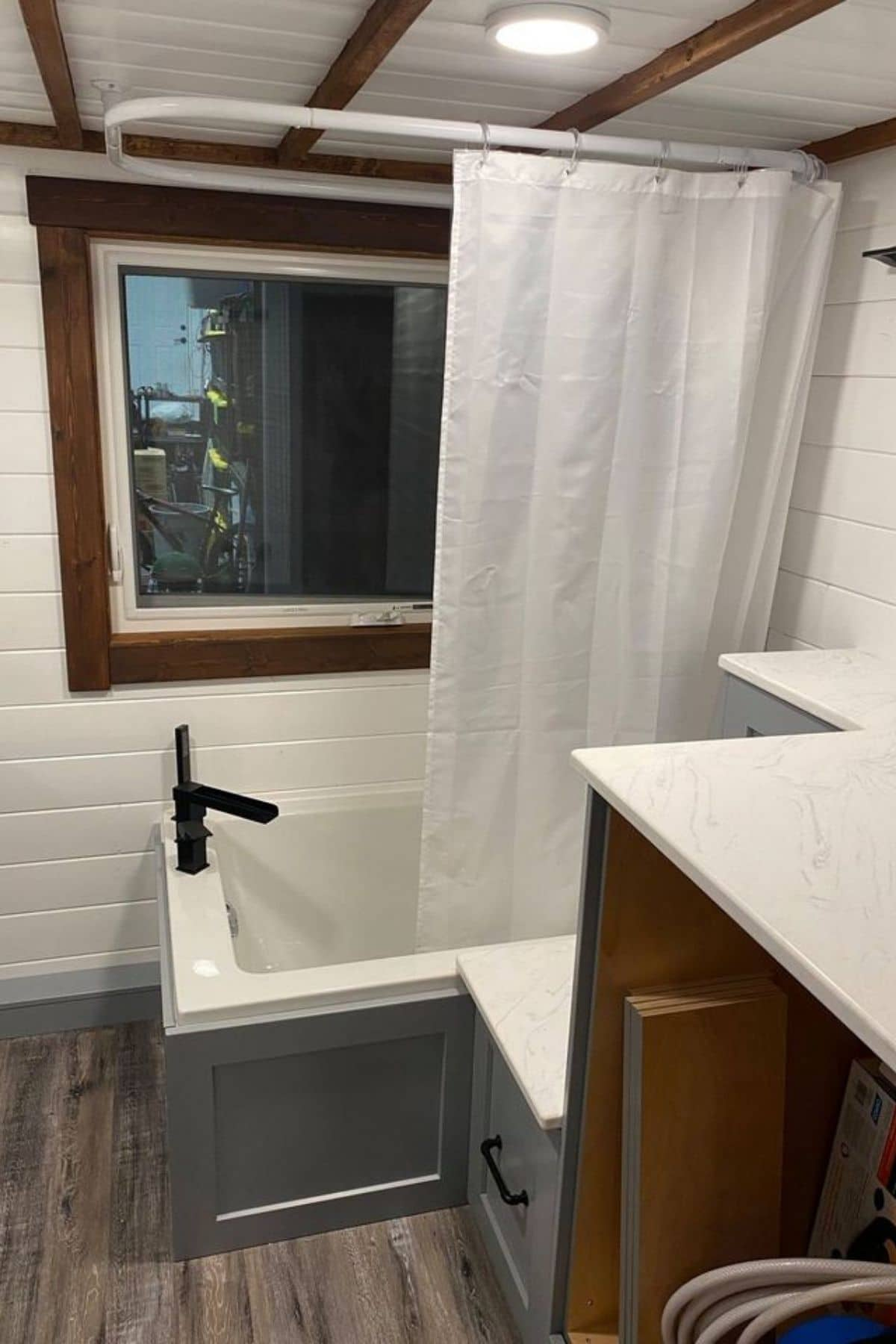 blue exterior on bathtub with curtain pulled halfway for shower