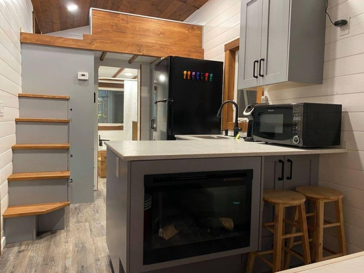 gray countertop with fireplace in kitchen and stairs on left side