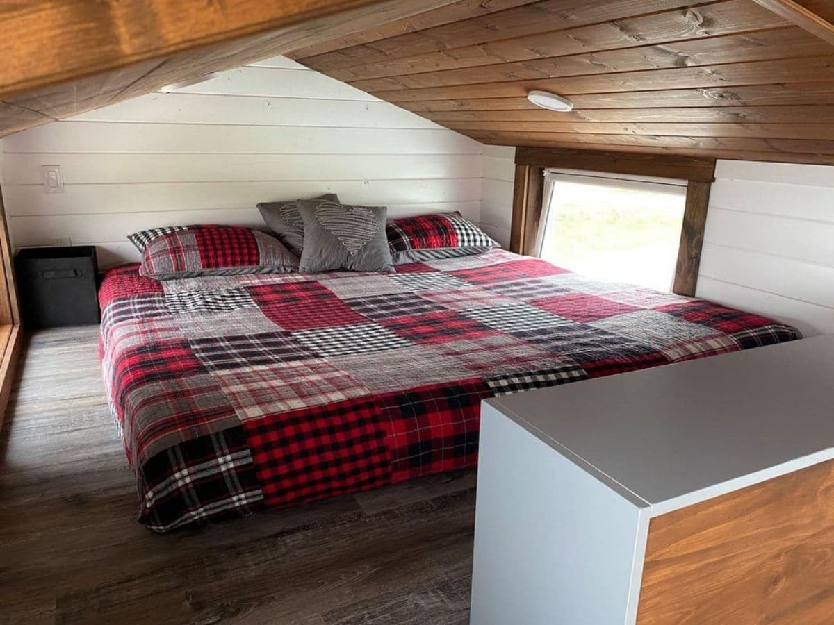 view into loft with king sized bed with red plaid blanket