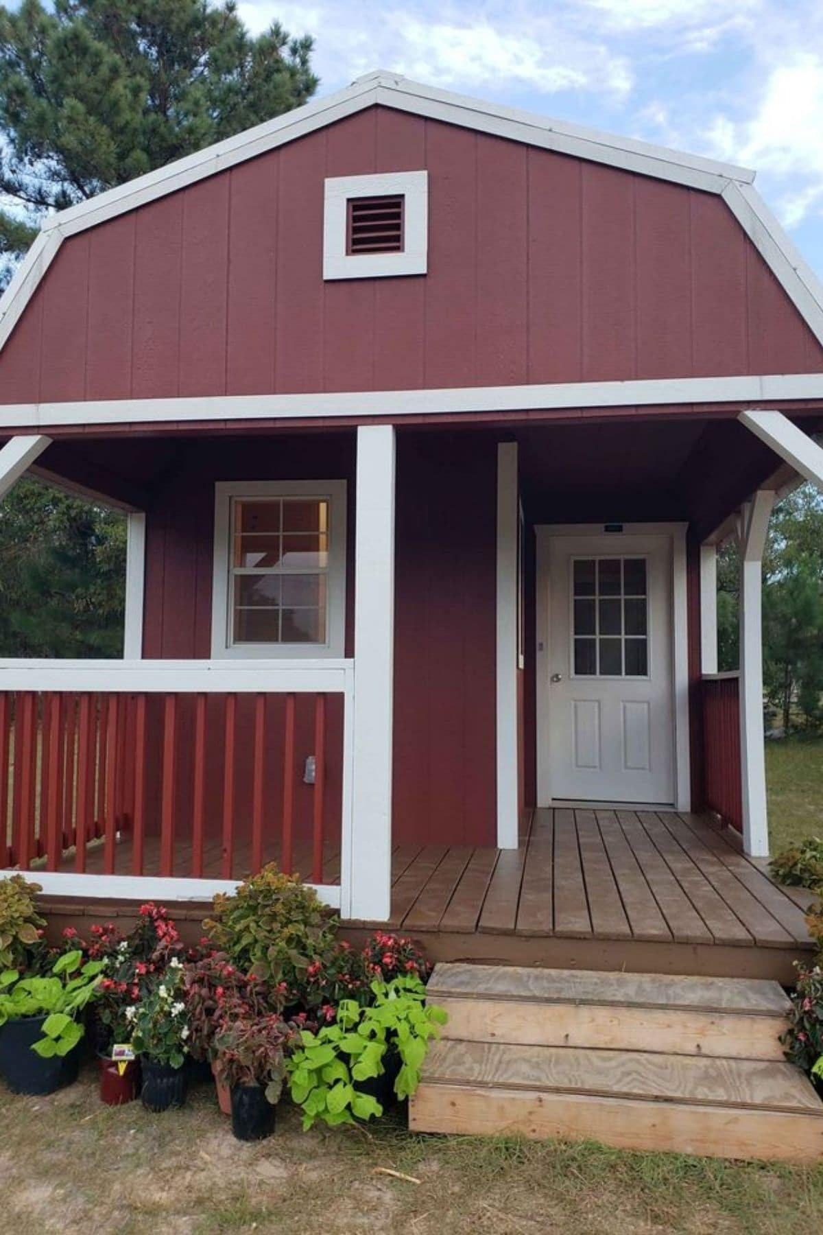 front of red barn style tiny house with front porch