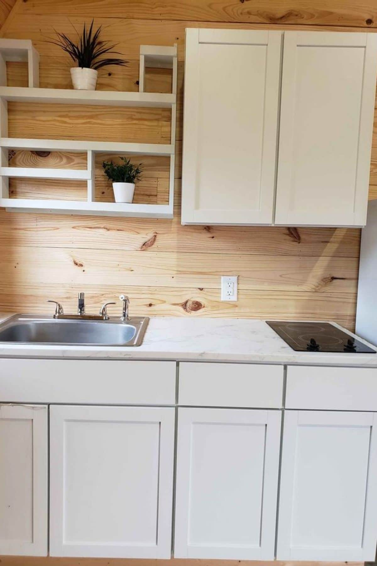 close up of sink with 2-burner cooktop on white cabinets