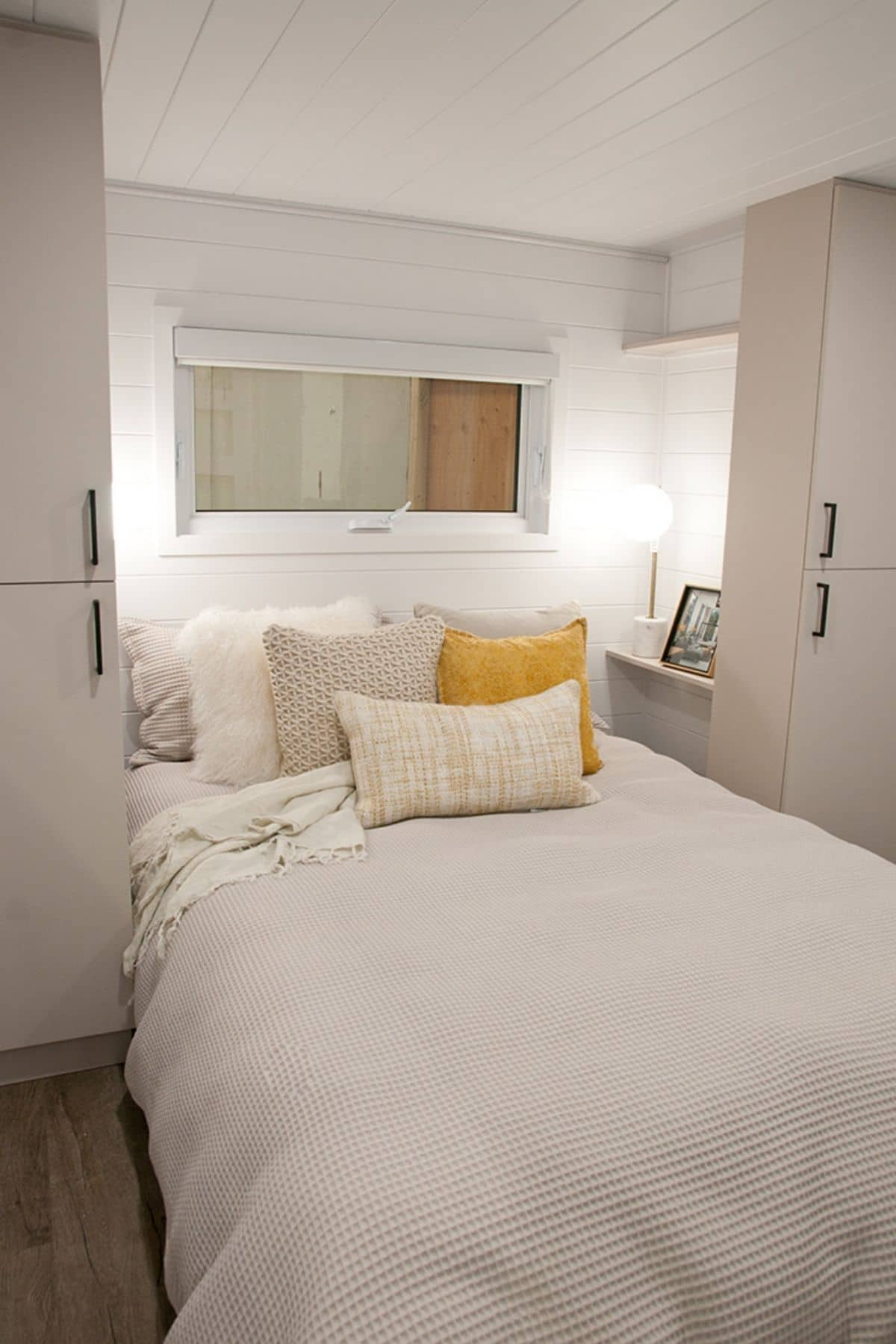 White linens on bed between white cabinets in tiny house bedroom