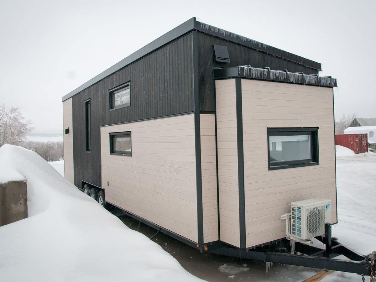 cream and black siding on tiny house by snow