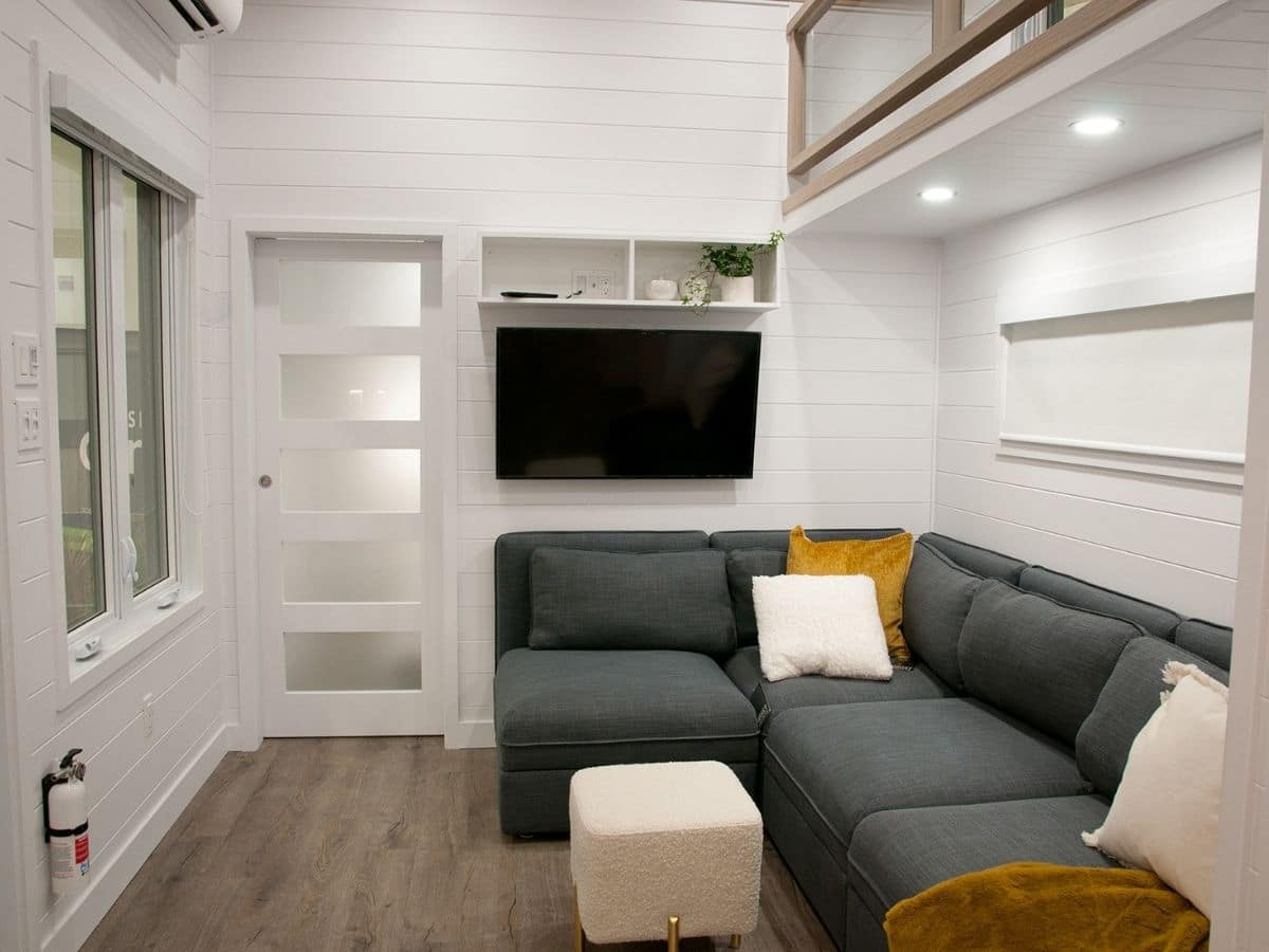blue sofa against white wall inside door of tiny home