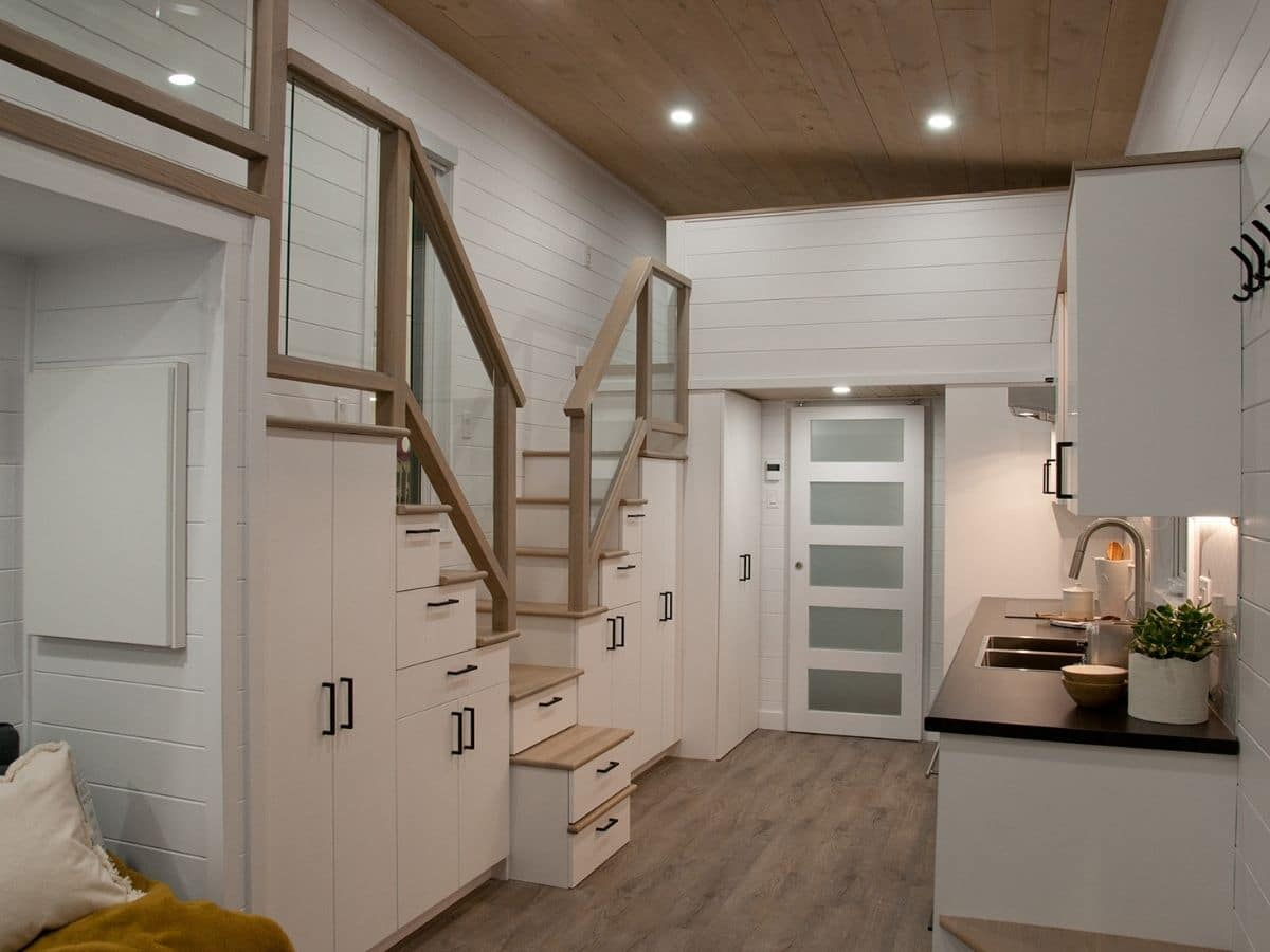 cabinets underneath white stairs going on both sides of tiny home