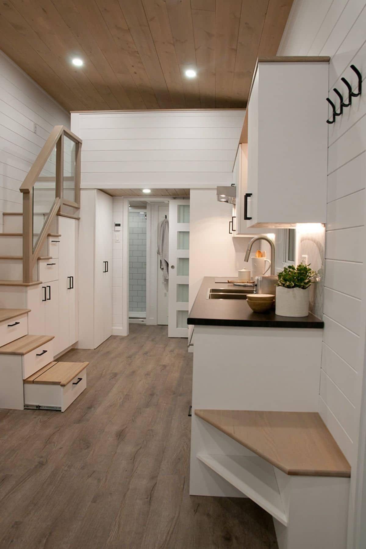 kitchen along right side of tiny home with white cabinets and butcher block tops