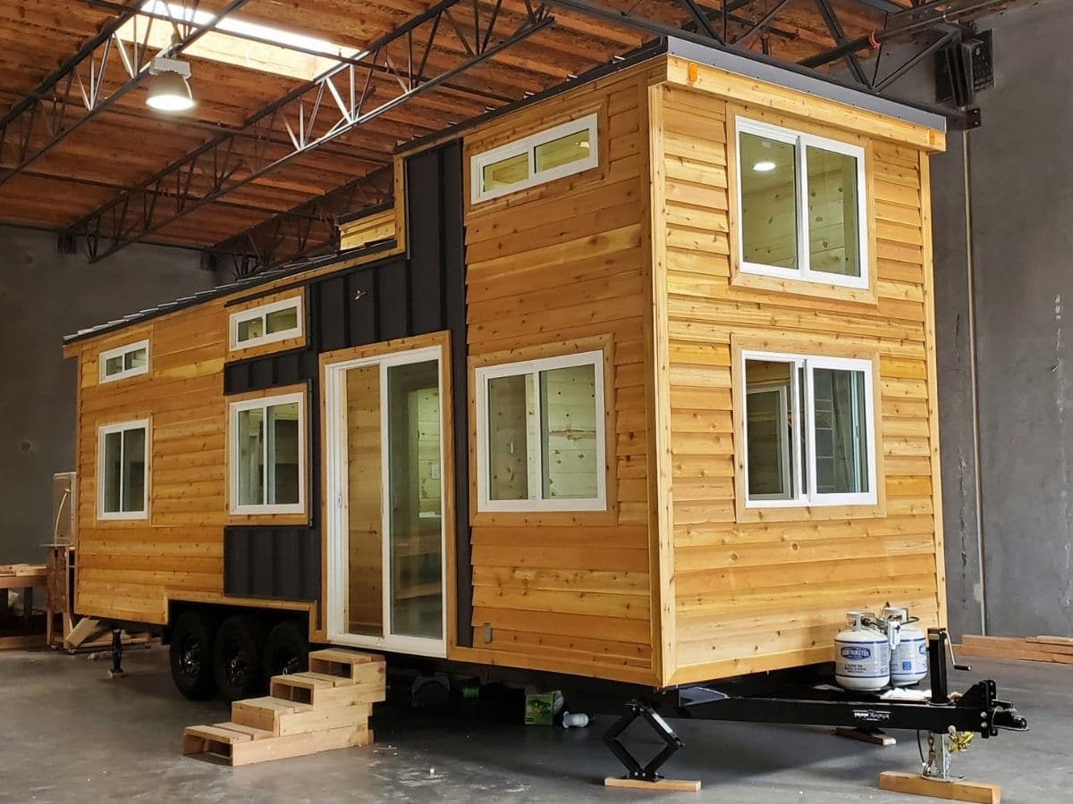 tiny home with wood siding and black trim in warehouse