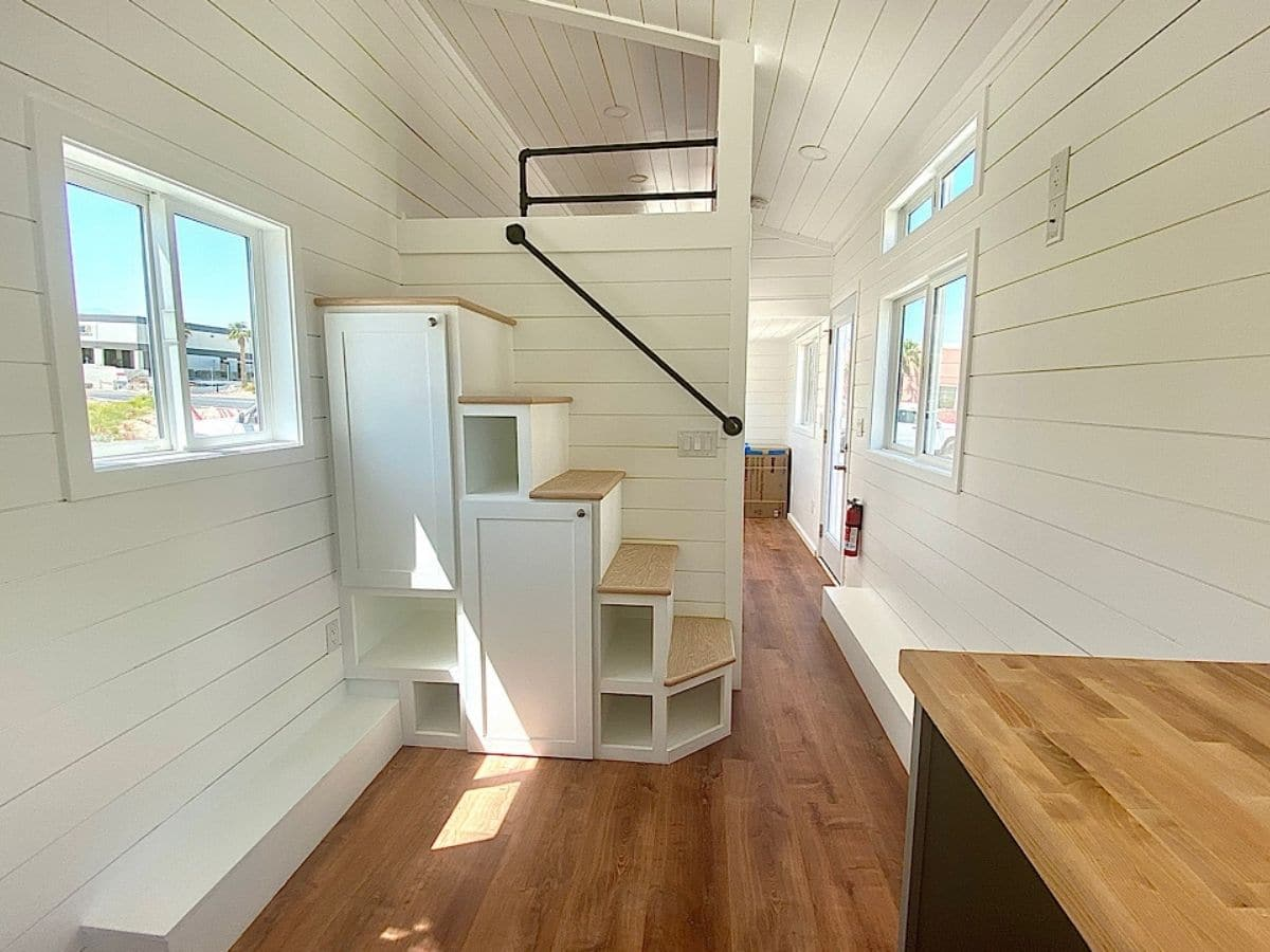 white stairs leading to loft with open storage cubbies