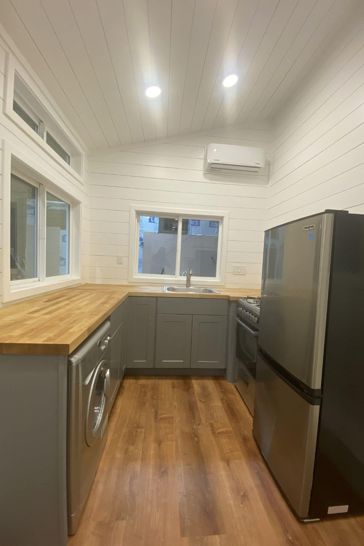 u-shaped kitchen with gray cabinets and stainless steel refrigerator on right
