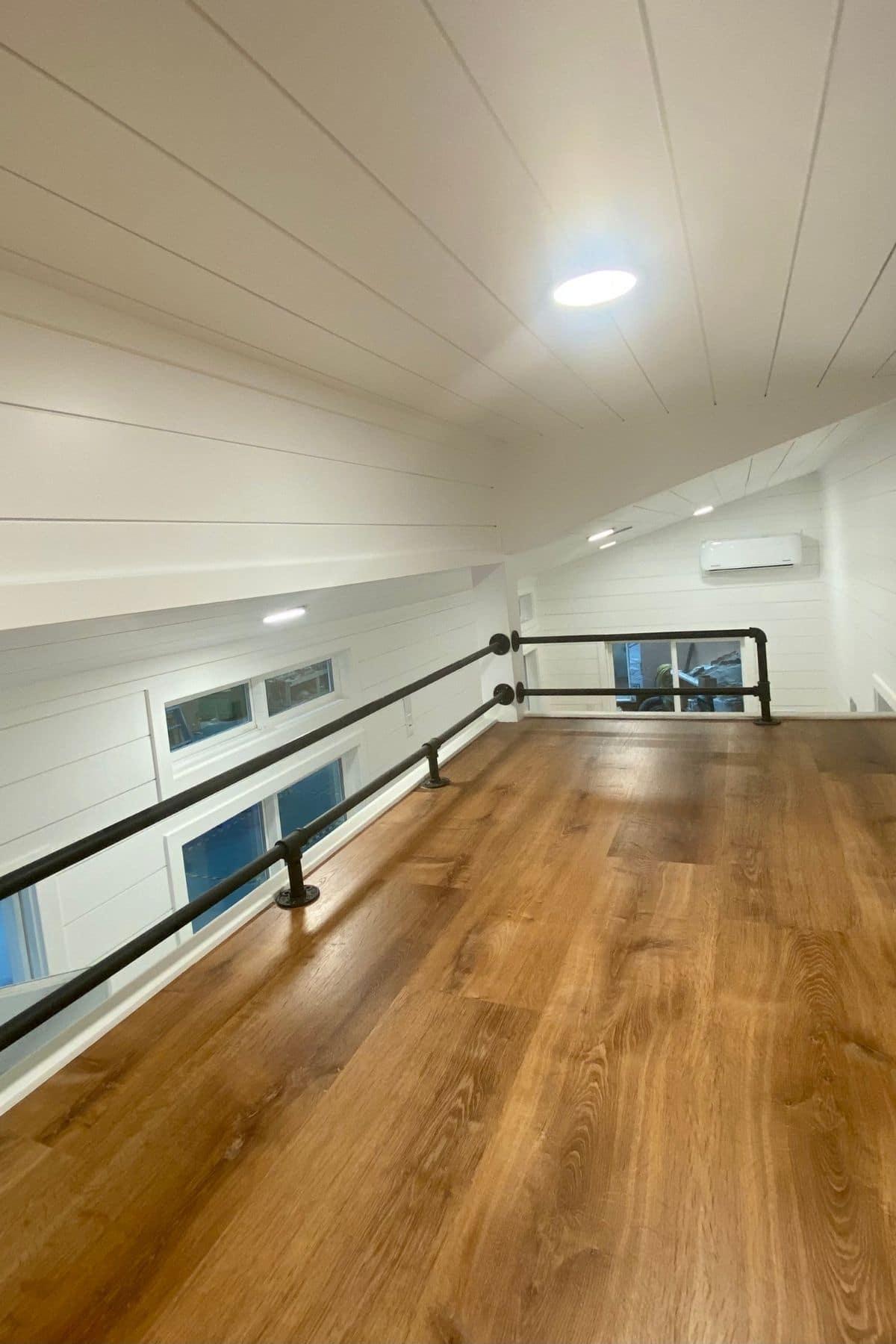 view across loft with black matte railing on left side