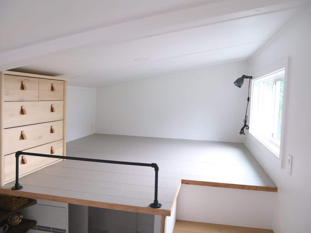 white loft with wood chest of drawers against walls