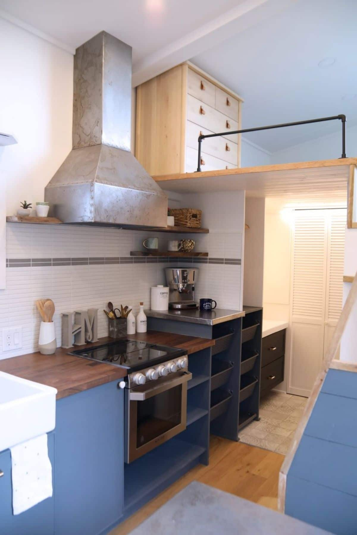 light blue cabinets with butcher block tops in kitchen with white walls