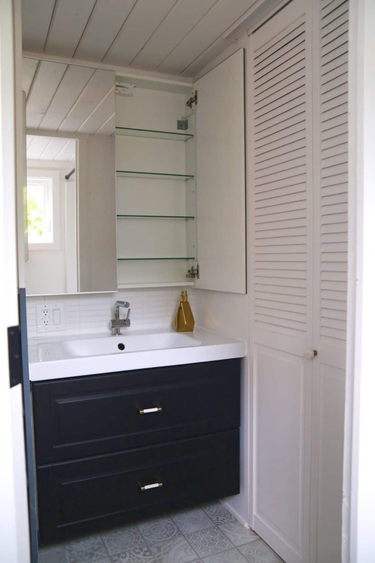 dark blue drawers under white sink with open medicine cabinet