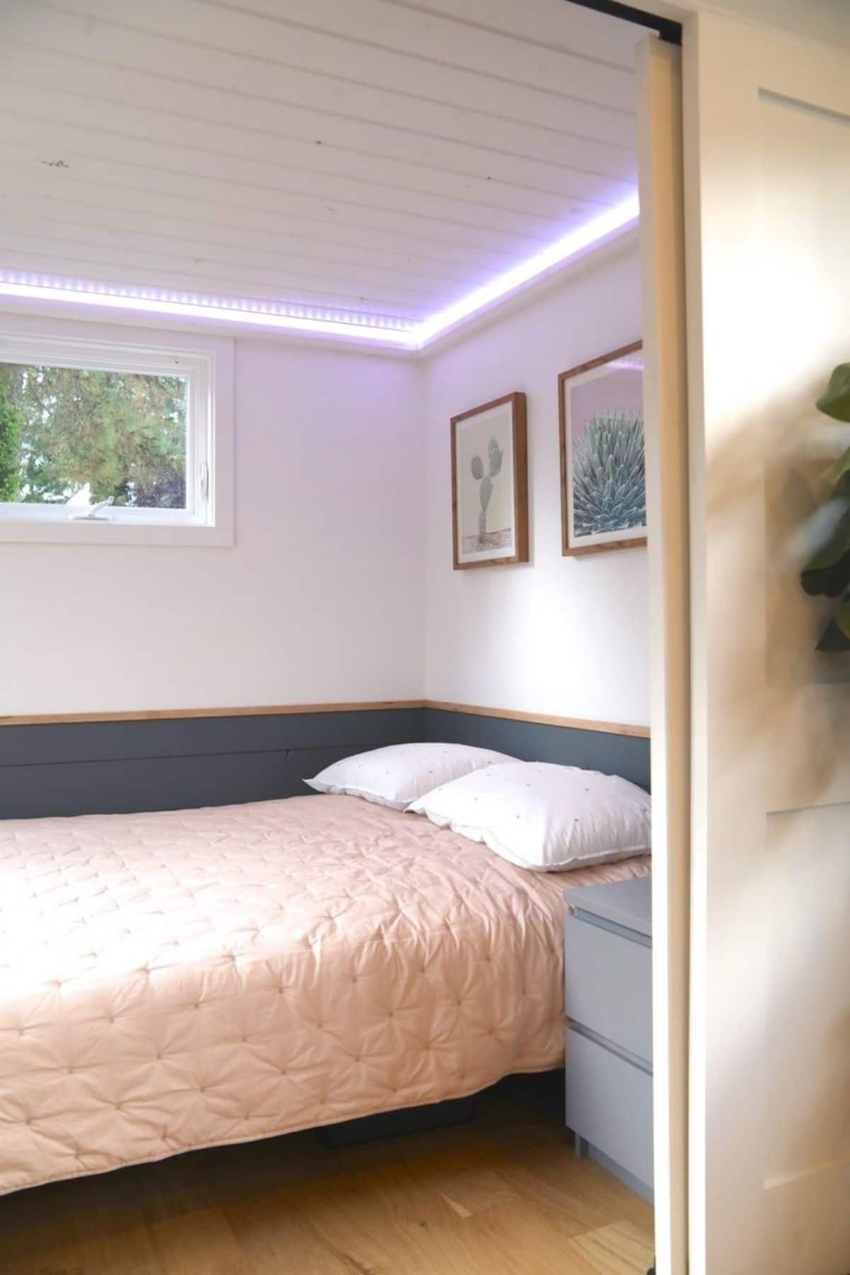 looking through door to small bedroom with bed next to blue chest of drawers