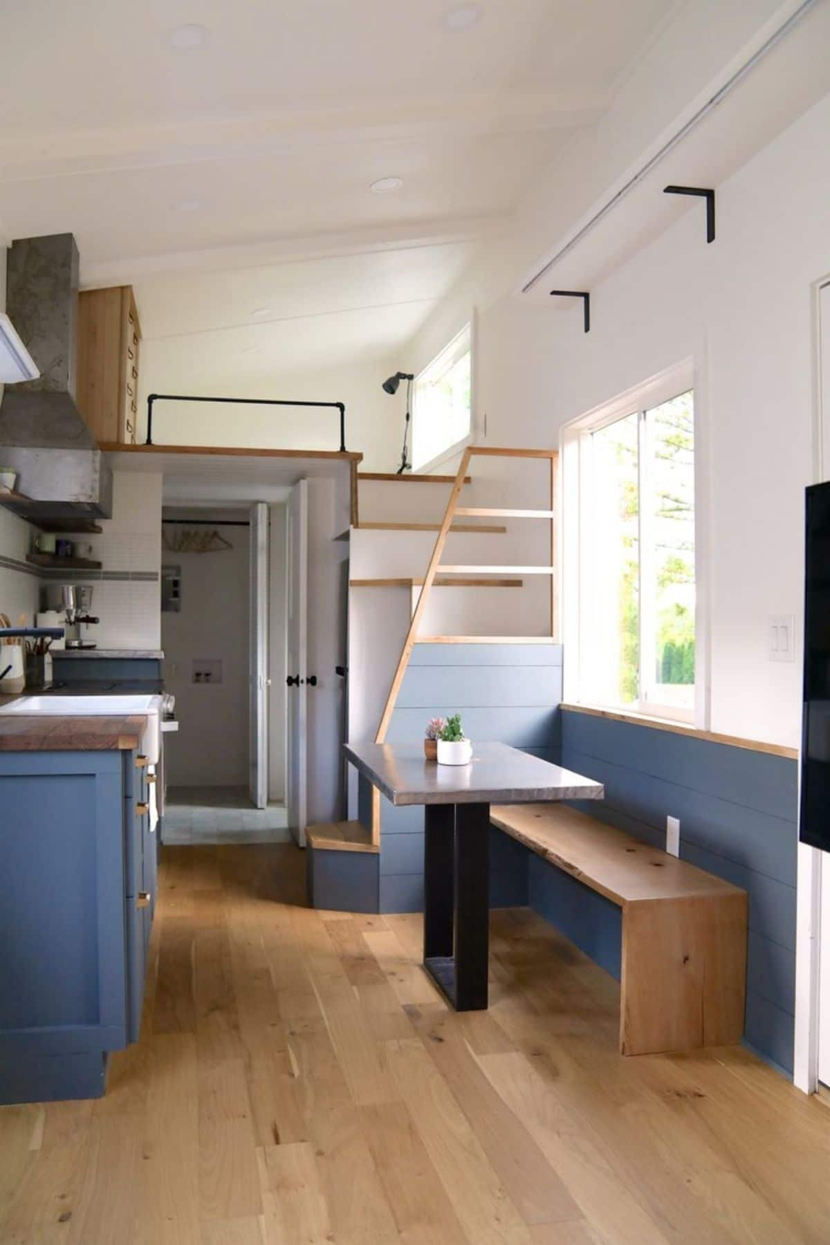 kitchen dining booth between door and stairs with blue cabinets and background