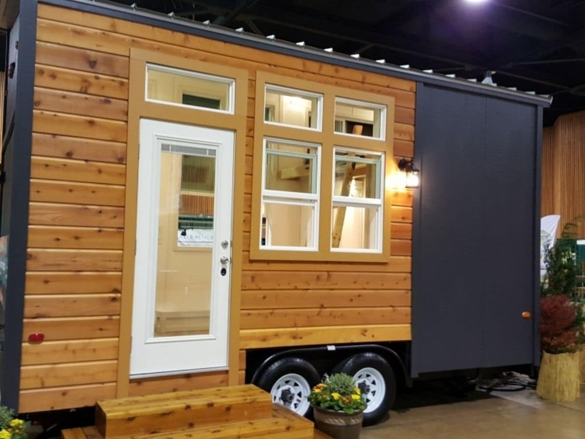 gray and wood grain tiny home with white door in show room