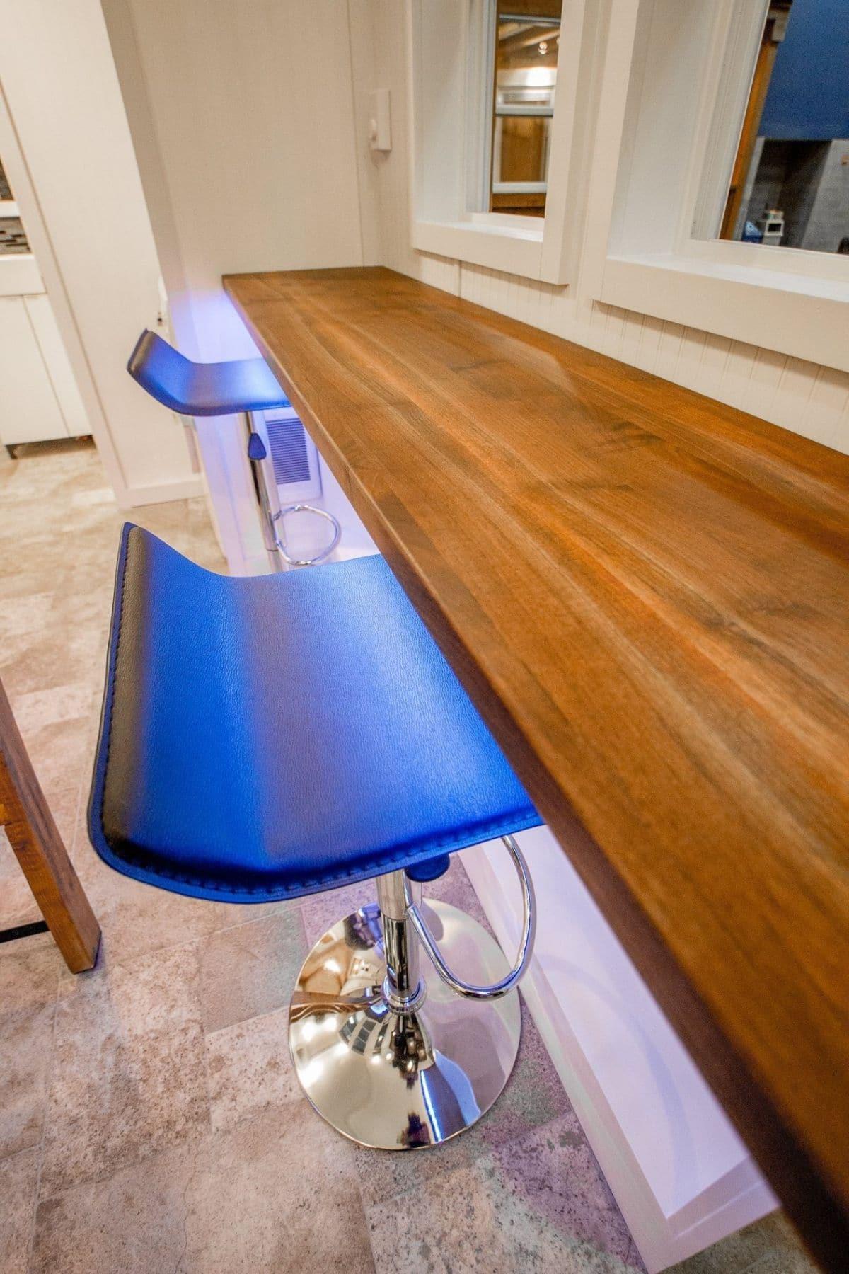 butcher block bar above black stools with blue light under bar