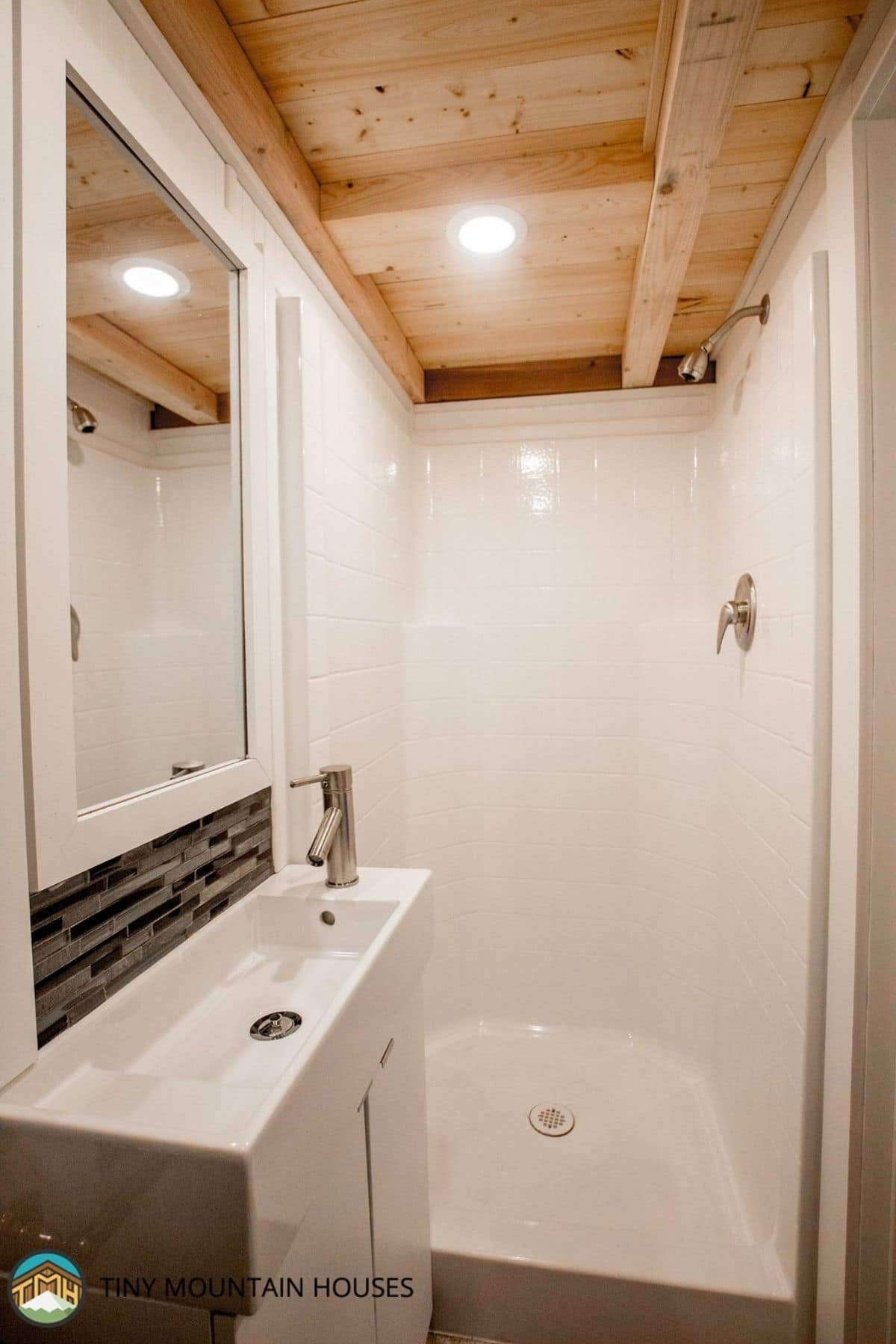 white shower stall next to white sink with blue and gray tile backsplash