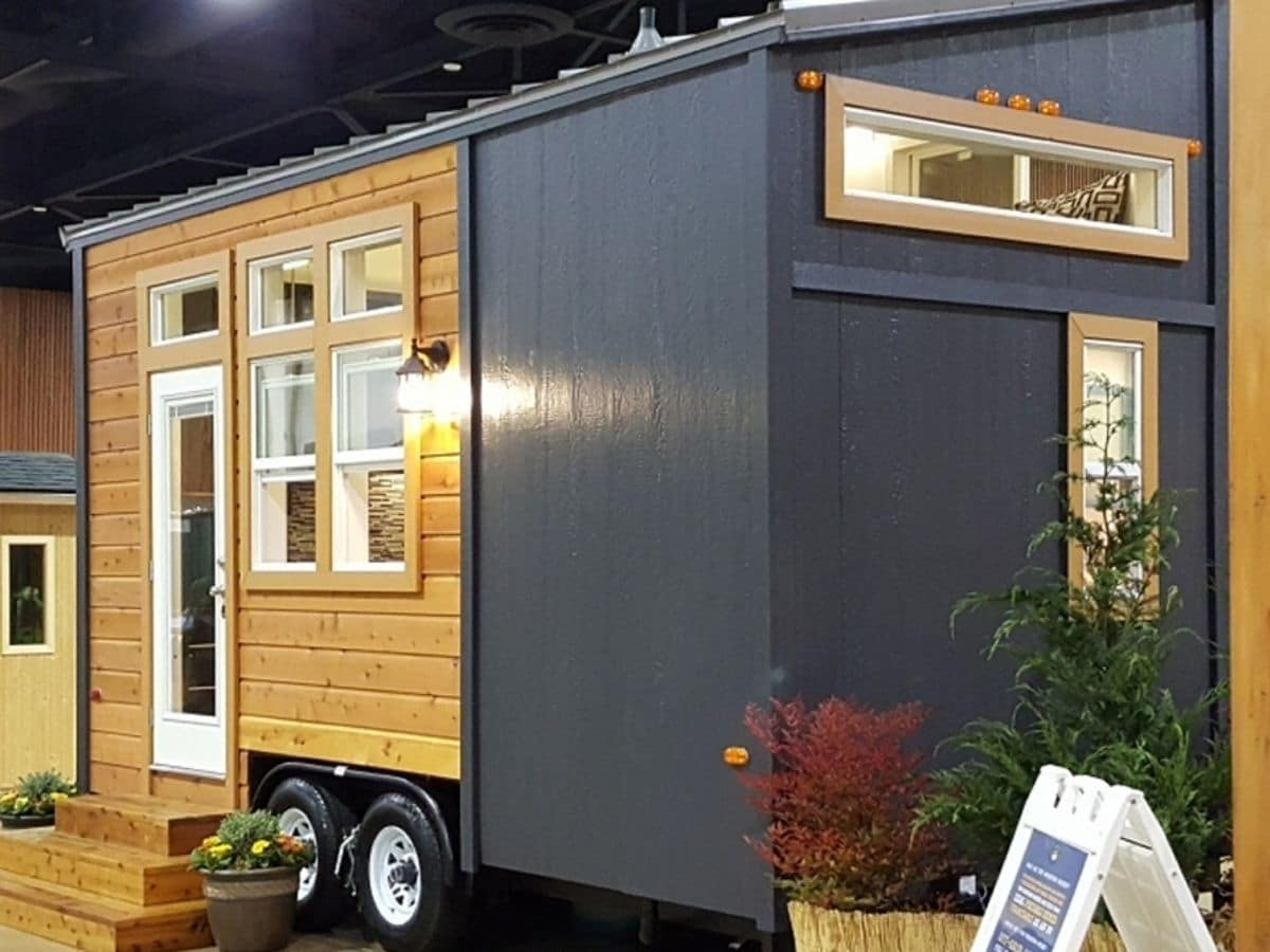 end of tiny home with gray siding and wood siding