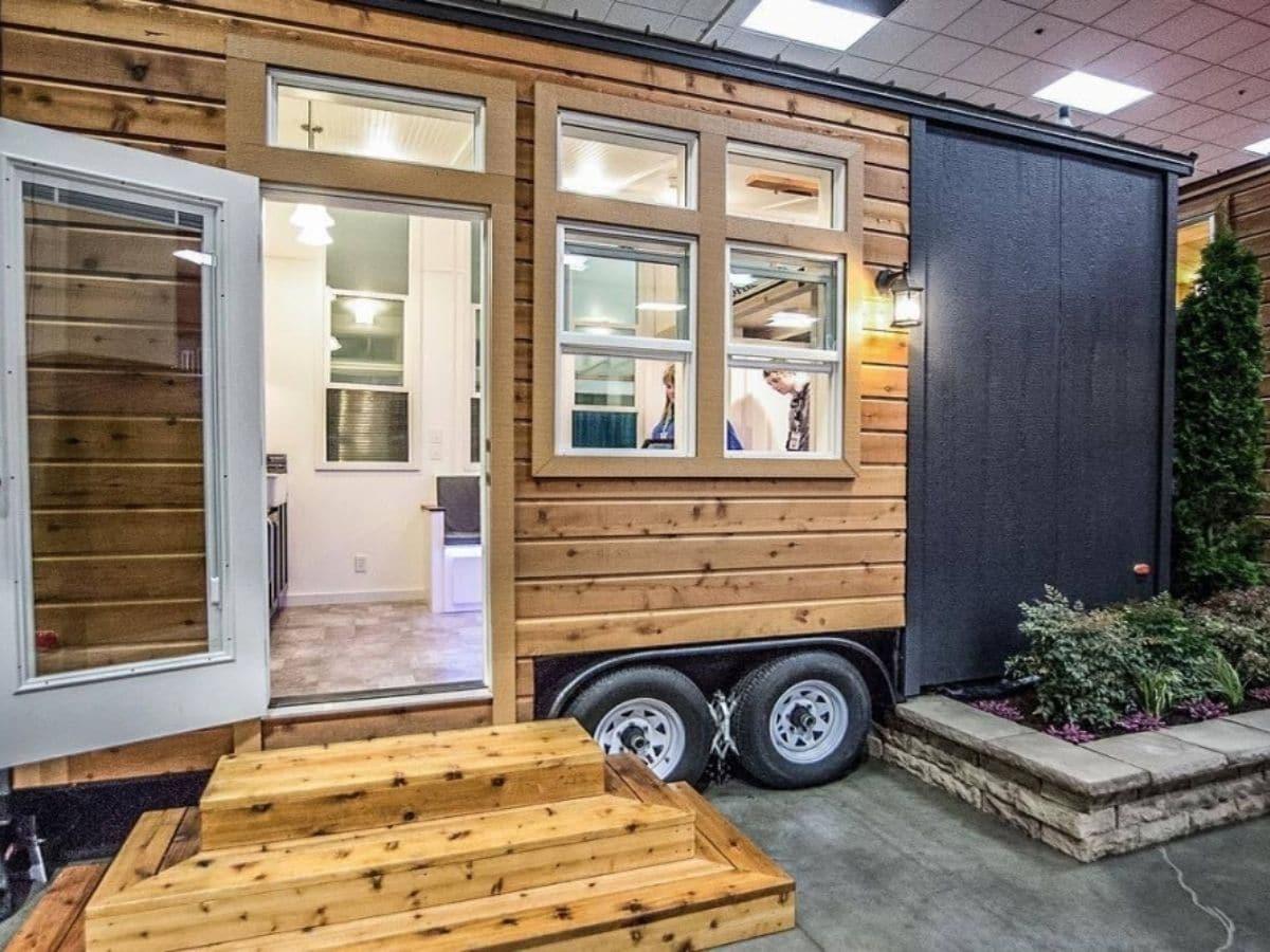 whtie front door on wood grain and gray siding tiny home in showroom