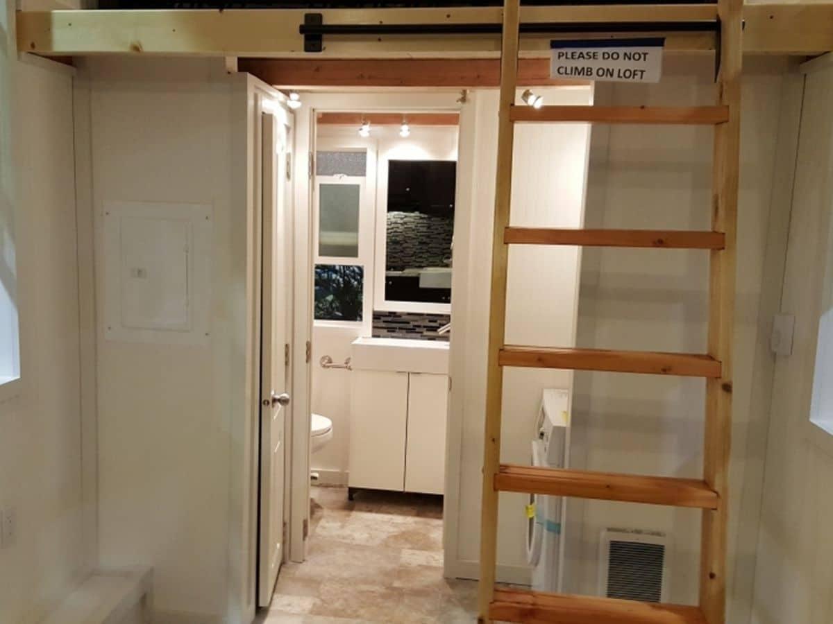 wood ladder to loft above tiny home bathroom