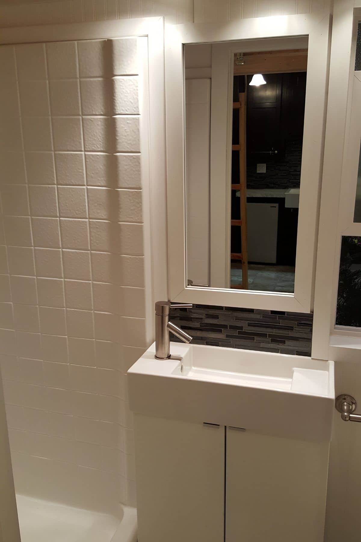 white tile wall next to white sink with mirror above vanity