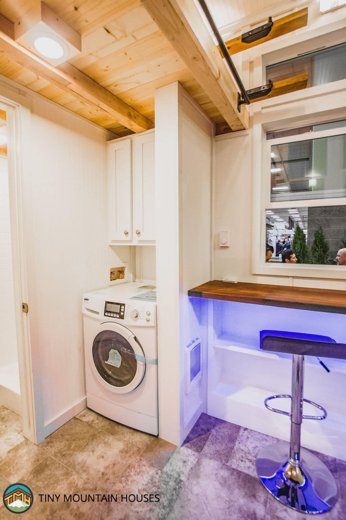 combination washer and dryer below cabinet next to bar with blue light underneath