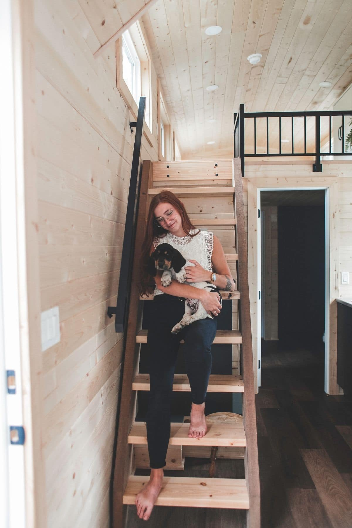 woman carrying dog down stairs