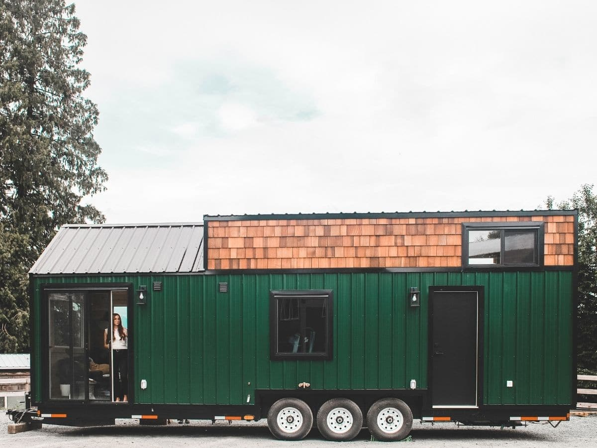 woman leaning out door of green tiny house with wood roof