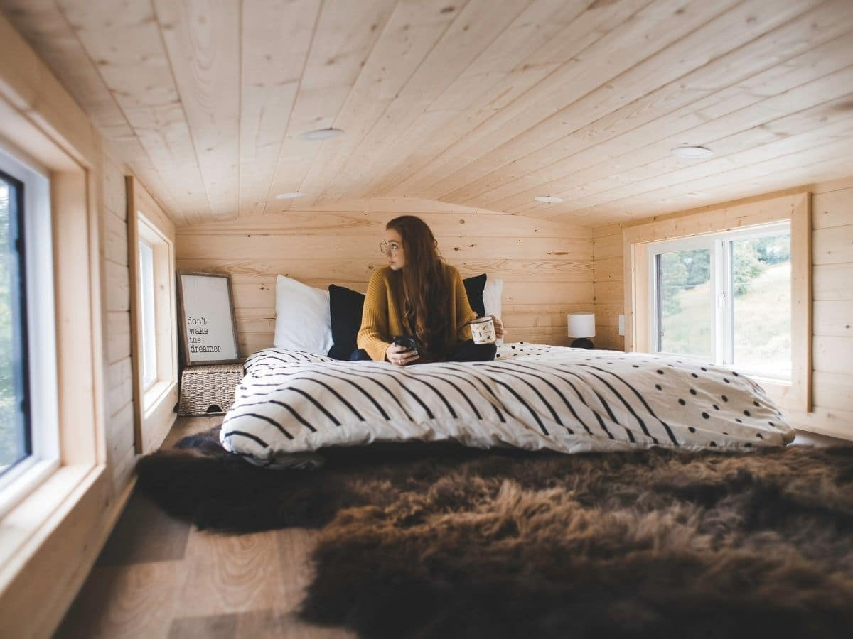 woman on bed in loft with fur rug by stairs