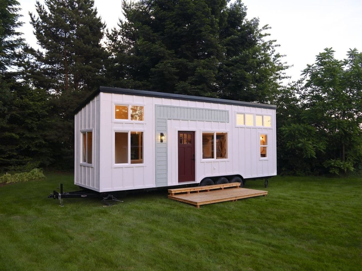 tiny home on graass with white siding and multiple windows