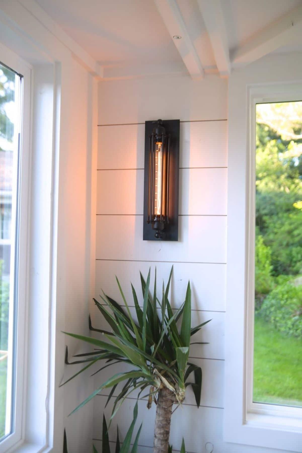 wall light between windows against white shiplap