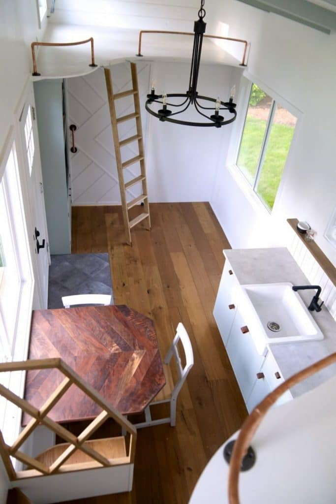 view from loft above bathroom down into main living space with kitchen on right and table on left