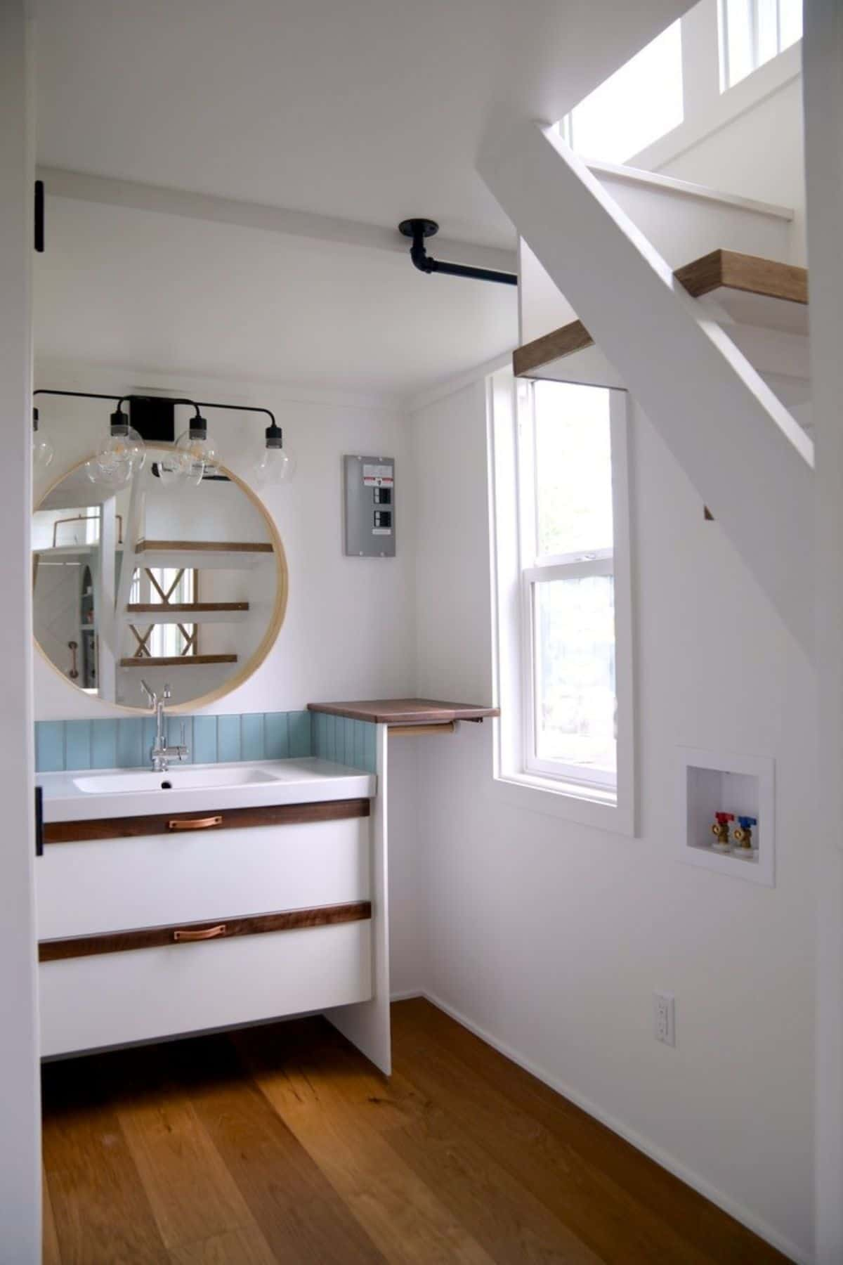 view into bathroom behind stairs with vanity against wall