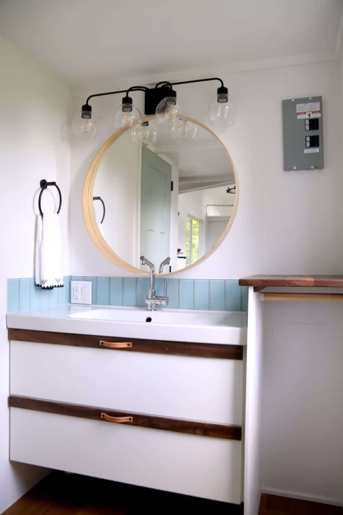 Vanity against white wall with gold accents and round mirror above