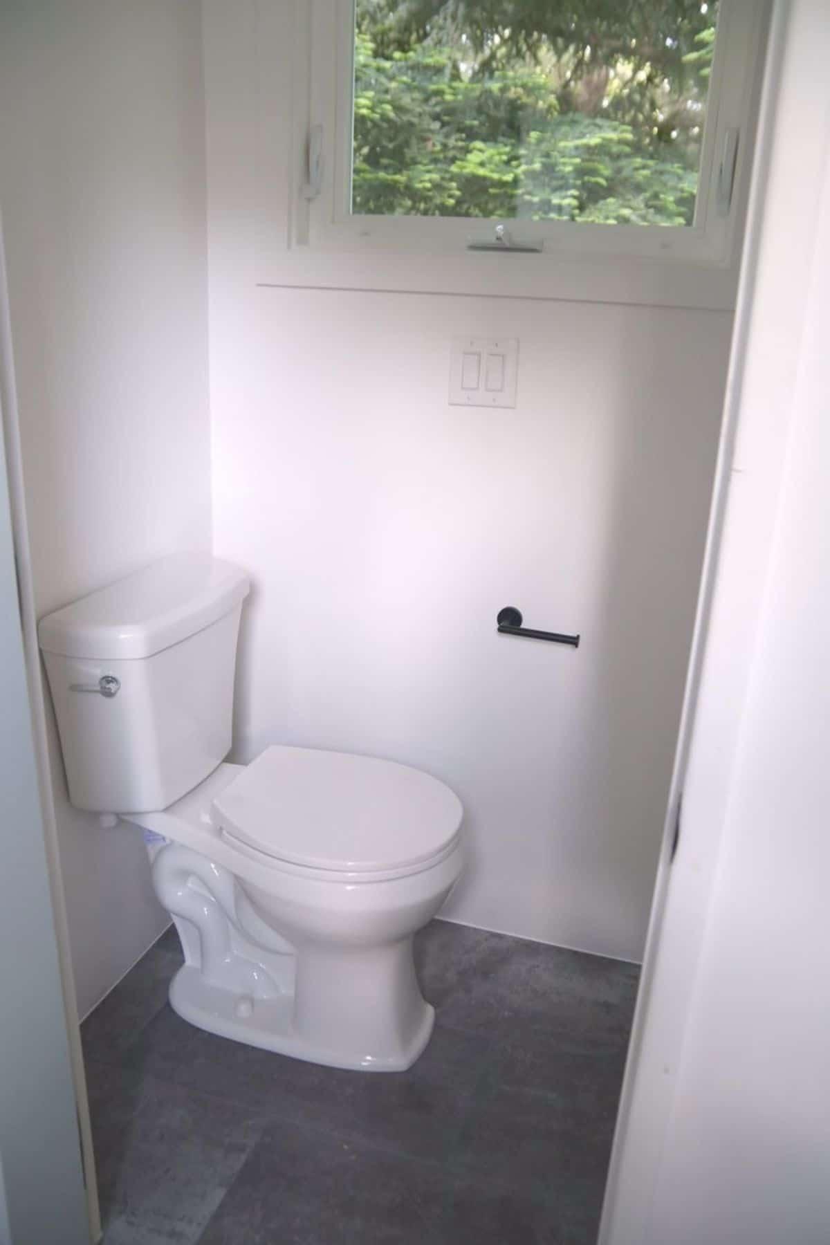 flush toilet against white wall below window